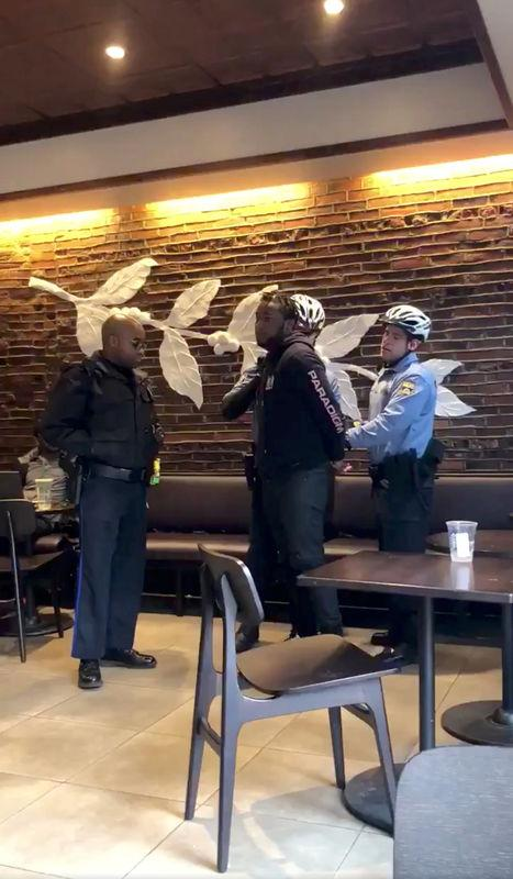 Police officers detain a man inside a Starbucks cafe in Philadelphia