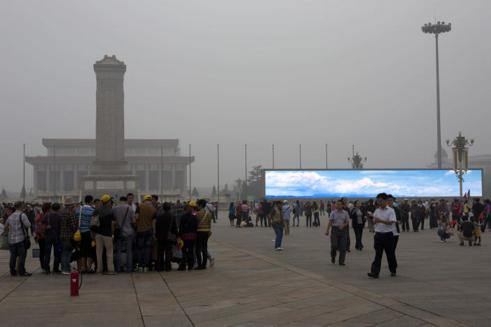 "In this photo taken on Sept. 13, 2013 tourists visit Tiananmen Square on a hazy day while an electronic screen shows a blue sky and white clouds as part of a propaganda video in Beijing, China. China's tourism industry has grown at a fast pace since the country began free market-style economic reforms three decades ago. However, it's latest tourism slogan ""Beautiful China"" has been derided as particularly inept at a time when record-busting smog has drawn attention to the environmental and health costs of China's unfettered industrialization. Some point to unsophisticated marketing as an explanation. (AP Photo/Alexander F. Yuan)"