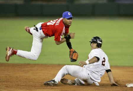 Cuba's second baseman Yulieski Gourriel (L) throws the ball as Venezuela's Rene Pinto slides into second base during the fifth inning in a baseball game of the Olympic qualifier tournament of the Americas in Havana in this September 1, 2006 file photograph. REUTERS/Enrique De La Osa/Files