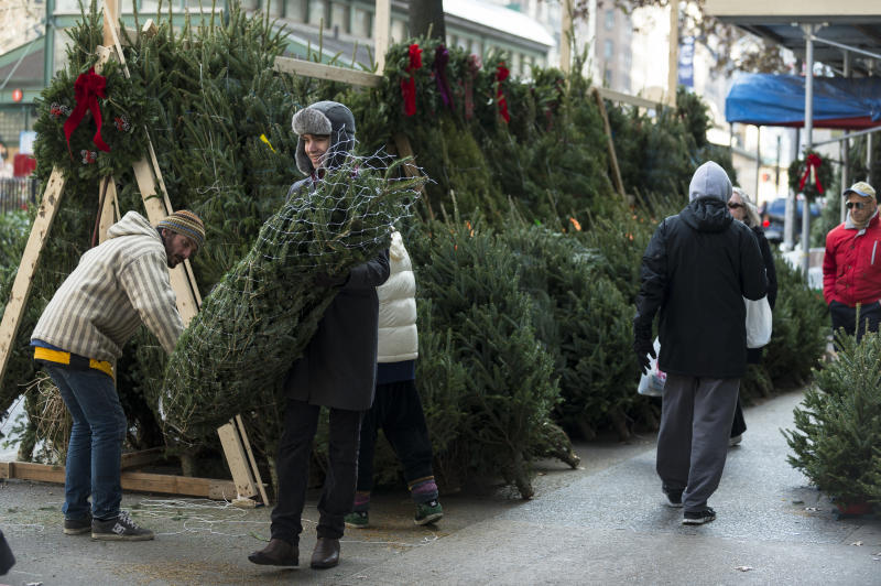 A resident of Manhattan's Upper West Side purchases a Christmas tree from a street vendor on Friday, November 29, 2013. (Photo by Angelo Merendino/Corbis via Getty Images)