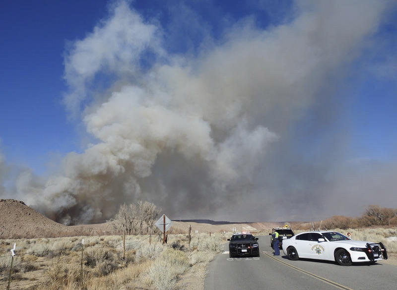 This Sunday, Feb. 18, 2018, photo taken by the Bishop California Highway Patrol and released by the Inyo County Sheriff's Office shows smoke rising from wildfires near Bishop, Calif. A wind-driven wildfire in rural central California forced mandatory evacuations and threatened hundreds of buildings Monday, including a historic railroad station, after it tripled in size overnight, officials said. (Bishop California Highway Patrol via AP)