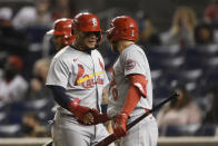 St. Louis Cardinals' Yadier Molina, left, is greeted by Austin Dean (0) after he scored on a triple by Dylan Carlson during the seventh inning of the team's baseball game against the Washington Nationals, Tuesday, April 20, 2021, in Washington. (AP Photo/Nick Wass)