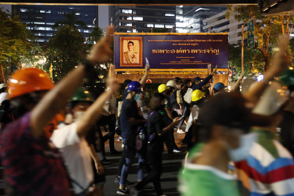Pro-democracy demonstrators flash a three-finger salute of defiance in front of the Thai king's portrait as they march to the German Embassy in central Bangkok, Thailand, Monday, Oct. 26, 2020. As lawmakers debated in a special session in Parliament that was called to address political tensions, student-led rallies were set to continue with a march through central Bangkok on Monday evening to the German Embassy, apparently to bring attention to the time King Maha Vajiralongkorn spends in Germany. (AP Photo/Gemunu Amarasinghe)