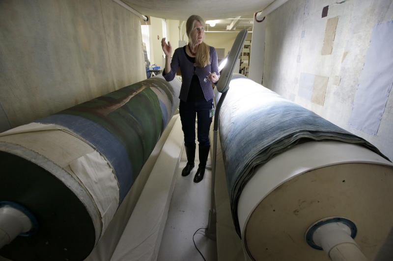 """In this Tuesday, Nov. 7, 2017 photo textile conservator Kate Tarleton, of Rochester, Mass., stands between two oversized spools holding a portion of the 1848, """"Grand Panorama of a Whaling Voyage Round the World,"""" at the museum in New Bedford, Mass. The quarter-mile-long (0.4-kilometer-long) panorama toured the U.S. after it was completed in 1848. . (AP Photo/Steven Senne)"""