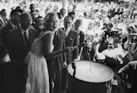 <p>Marilyn was the guest of honor at a ribbon-cutting ceremony for the Time-Life Building in New York City. She's lighting the giant firecracker with a giant match. </p>
