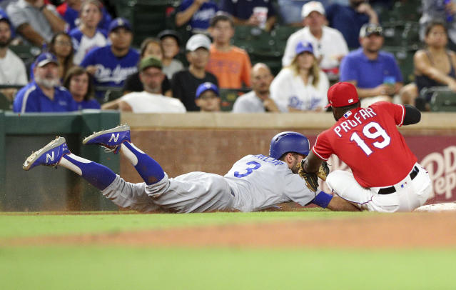 Los Angeles Dodgers' Chris Taylor (3) makes it back to third ahead of the tag by Texas Rangers third baseman Jurickson Profar (19) in the fourth inning of a baseball game Tuesday, Aug. 28, 2018, in Arlington, Texas. (AP Photo/Richard W. Rodriguez)