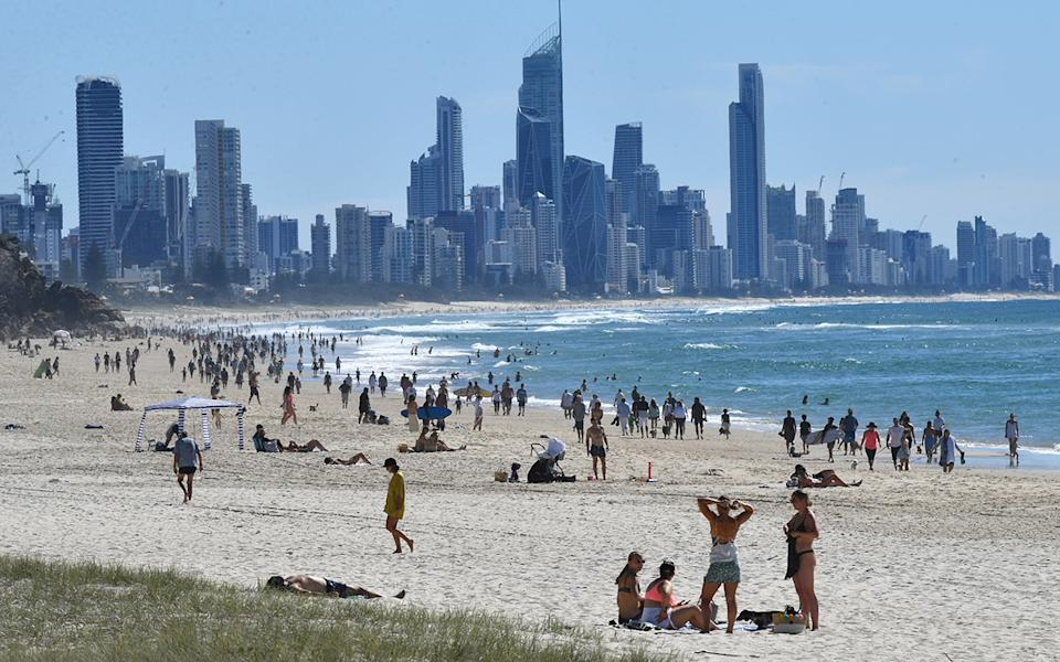 People are seen on the beach at Burleigh Heads on the Gold Coast, Sunday, May 3, 2020.  The Queensland Government have relaxed some restrictions due to a very low number of new COVID-19 infections. Queenslanders can now go for a drive (within 50km of home), ride a motorbike, jetski or boat for recreation, have a picnic, visit a national park and shop for non-essential items. (AAP Image/Darren England) NO ARCHIVING