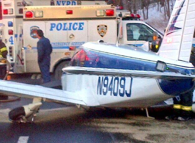 In this photo downloaded from the New York City Police Department's Twitter account, a light airplane's fuselage rests on the roadway after its pilot made an emergency landing on the Major Deegan Expressway in the Bronx borough of New York, Saturday, Jan. 5, 2014. Officials said that there were no serious injuries after the Piper PA-28, set down at around 3:20 p.m. on the northbound side of the highway. After safely removing the fuel from the aircraft, a flatbed truck eventually carried the plane off the highway. (AP Photo/New York City Police Department)