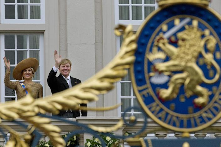 The royal coat of arms is seen in the foreground as Netherlands' King Willem-Alexander and his wife Queen Maxima wave to well wishers from the balcony of Noordeinde Palace, after the King officially opened the new parliamentary year with a speech outlining the government's plan and budget policies for the year ahead in The Hague, Netherlands, Tuesday, Sept. 17, 2013. (AP Photo/Peter Dejong)