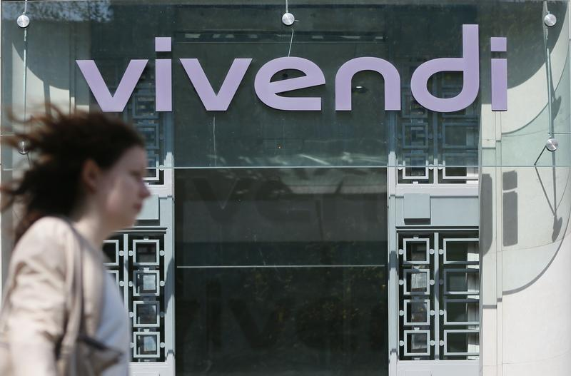 A woman walks walk past the main entrance of the entertainment-to-telecoms conglomerate Vivendi's headquarters in Paris April 8, 2015. REUTERS/Gonzalo Fuentes