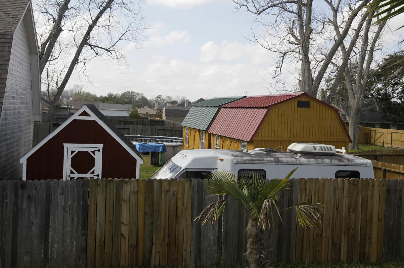 Three buildings and a travel trailer sit in the backyard of a Dayton, Texas, house Tuesday, Feb. 21, 2012, where 11 children, some of them reportedly found in restraints, were removed by children's protective services last month. A next door neighbor said that the buildings had electricity and that there were beds inside. Texas authorities said Tuesday, Feb. 21, 2012, that they removed 11 children last month from the home where a registered sex offender lives after they found eight confined in a small, dark bedroom with restraints tying some to their beds. One month after a raid on the house, authorities are still trying to determine how the children are related and why they were there, Child Protective Services spokeswoman Gwen Carter said. Along with the children, 10 adults were living in the one-story, 1,700-square-foot home. (AP Photo/Pat Sullivan)