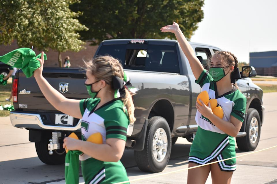 Smithville cheerleaders wore masks as they handed out toy footballs. (Photo: Angelica Matthews)