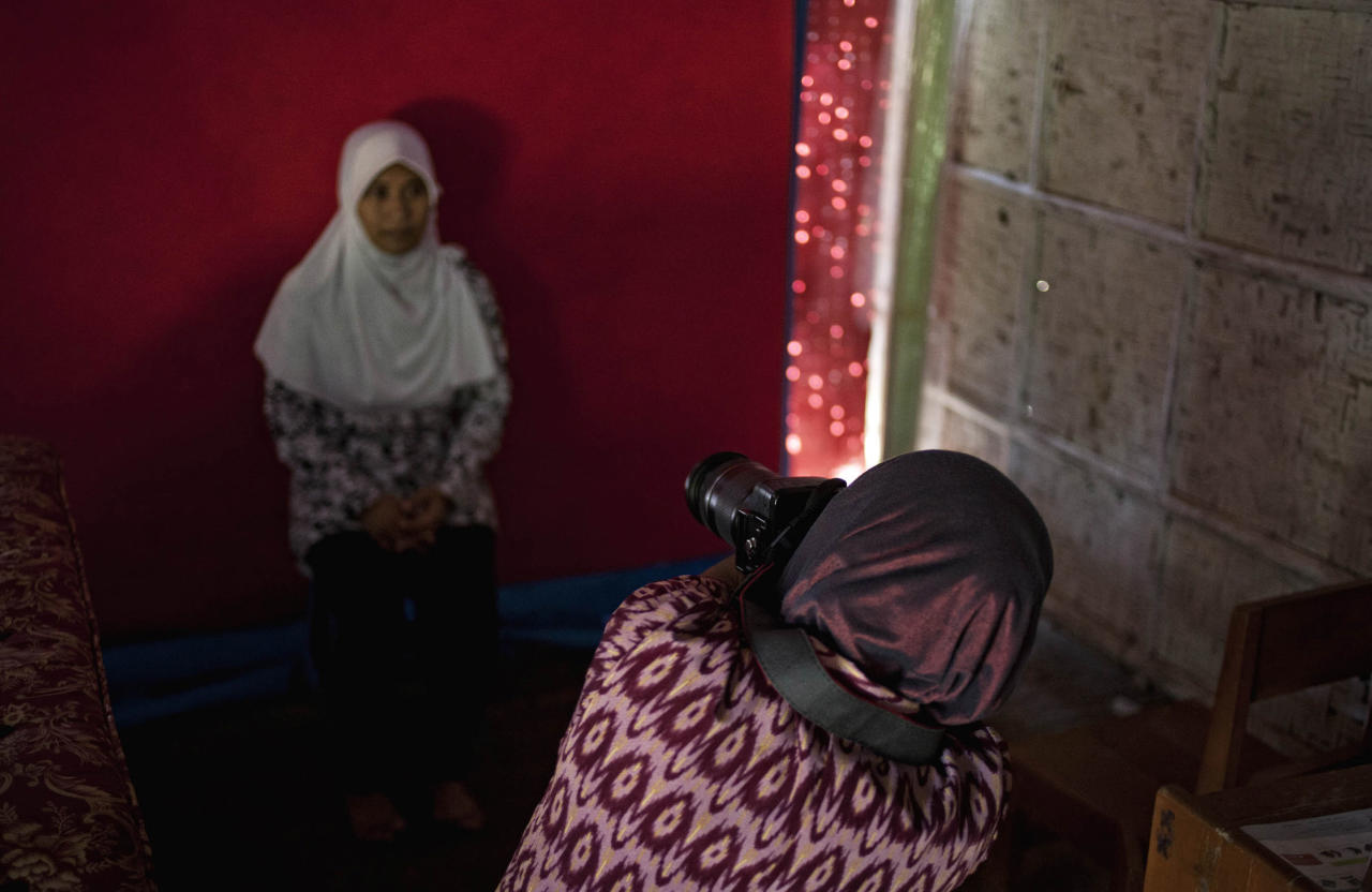 PURWOREJO, INDONESIA - MARCH 13:  Armless professional photographer Rusidah, 44, takes a customer's portrait on March 13, 2012 in Purworejo, Indonesia. Rusidah shoots weddings and parties and has a small studio at home in the village of Botorejo, Bayan District, Purworejo, Central Java where her husband and son also reside. She has been in the photography business for nearly 20 years.  (Photo by Ulet Ifansasti/Getty Images)