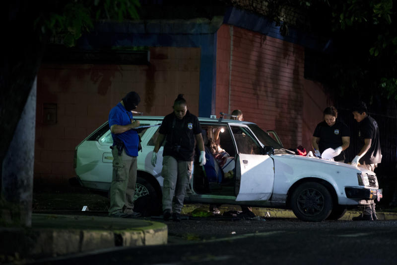 FILE - In this Aug. 20, 2018 file photo, forensic investigators examine the crime scene where a man was executed while driving his car, in San Salvador, El Salvador. President Donald Trump said that he is cutting off nearly $500 million in aid to Honduras, Guatemala and El Salvador help reduce immigration. The aid is meant to promote democracy-building, good governance, trade, agriculture, education, health and public safety and law enforcement. Experts say all of those areas play a direct role in whether people feel they can survive in their home country. (AP Photo/Rebecca Blackwell, File)