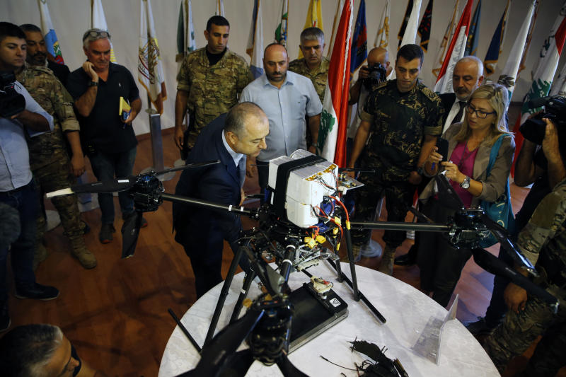 Lebanese Defense Minister Elias Bou Saab, center, points to parts of an Israeli drone that crashed in southern Beirut last month during a press conference to announce the results of an investigation into the incident, at the Lebanese Defense Ministry, in Yarzeh near Beirut, Lebanon, Thursday, Sept. 19, 2019. The investigation has concluded that two Israeli drones that crashed in the Lebanese capital last month were on an attack mission, one of them armed with 4.5 kilograms of explosives. (AP Photo/Bilal Hussein)