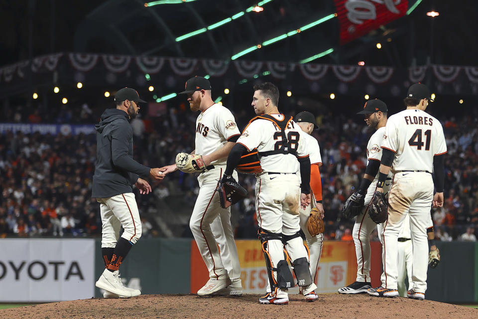 San Francisco Giants pitcher Zack Littell, second from left, hands the ball to manager Gabe Kapler as he is relieved during the eighth inning of Game 2 of a baseball National League Division Series against the Los Angeles Dodgers Saturday, Oct. 9, 2021, in San Francisco. (AP Photo/John Hefti)