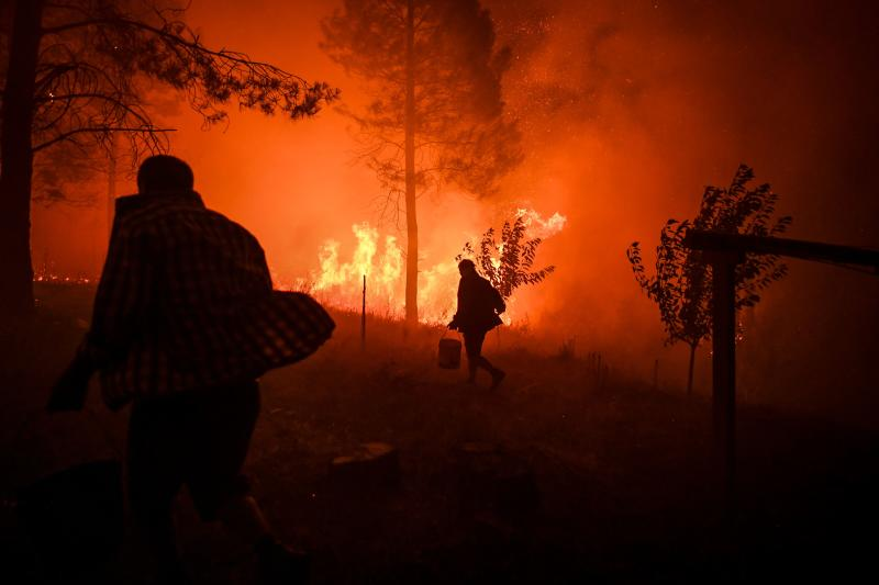 Villagers carry buckets with water to try extinguish a fire that was coming close to their houses at Amendoa in Macao, central Portugal on July 21, 2019. (Photo: Patricia De Melo Moreira/AFP/Getty Images)