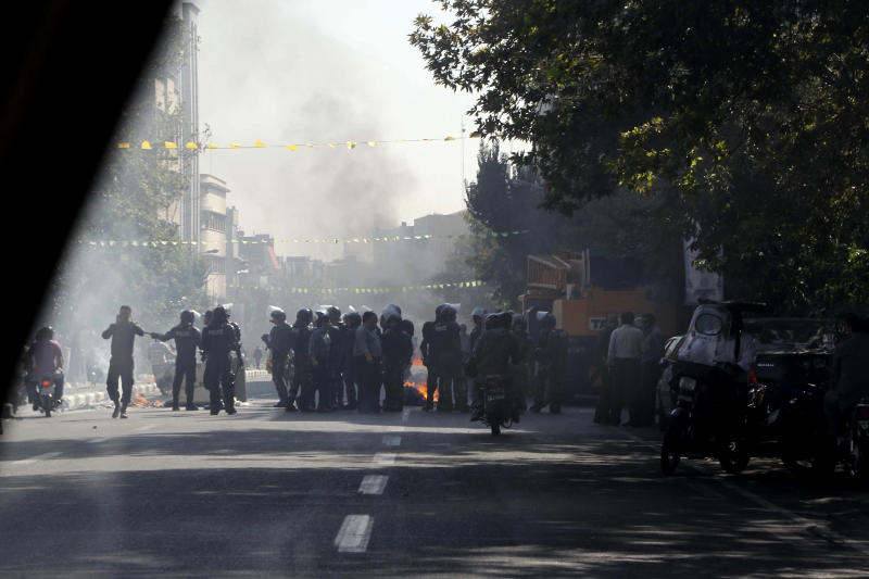 This photo, taken by an individual not employed by the Associated Press and obtained by the AP outside Iran shows Iranian police officers blocking a street as garbage cans are set on fire, in central Tehran, near Tehran's old main bazaar, on Wednesday, Oct. 3, 2012. Police threatened merchants who closed their shops in Tehran's main bazaar and launched crackdowns on sidewalk money changers on Wednesday as part of a push to halt the plunge of Iran's currency, which has shed more than a third its value in less than a week. (AP Photo) EDITORS NOTE AS A RESULT OF AN OFFICIAL IRANIAN GOVERNMENT BAN ON FOREIGN MEDIA COVERING SOME EVENTS IN IRAN, THE AP WAS PREVENTED FROM INDEPENDENT ACCESS TO THIS EVENT.