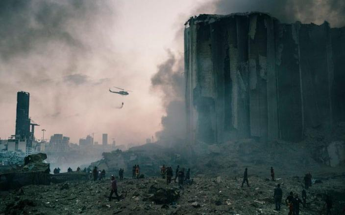 An army helicopter drops water at the smouldering scene of the explosion - EYEVINE