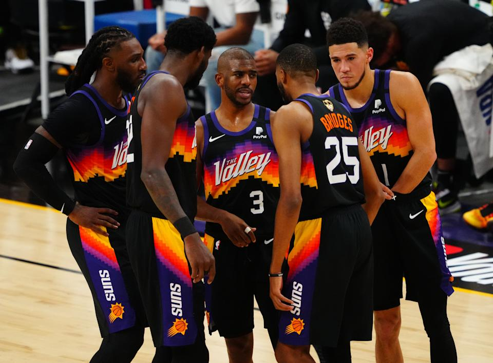 Chris Paul talks with Jae Crowder, Deandre Ayton, Mikal Bridges and Devin Booker in a huddle on the court.