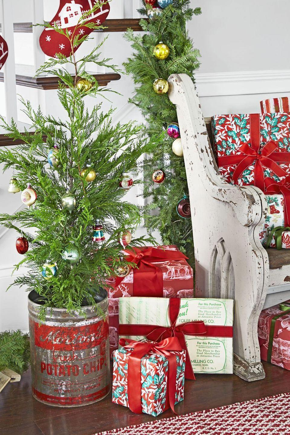 """<p>An old potato chip pail provides the perfect place for this <a href=""""https://www.countryliving.com/home-design/decorating-ideas/g316/decorate-mini-christmas-trees/"""" rel=""""nofollow noopener"""" target=""""_blank"""" data-ylk=""""slk:mini Christmas tree"""" class=""""link rapid-noclick-resp"""">mini Christmas tree</a>.</p><p><a class=""""link rapid-noclick-resp"""" href=""""https://go.redirectingat.com?id=74968X1596630&url=https%3A%2F%2Fwww.etsy.com%2Fmarket%2Fpotato_chip_bucket&sref=https%3A%2F%2Fwww.countryliving.com%2Fhome-design%2Fdecorating-ideas%2Fadvice%2Fg1247%2Fholiday-decorating-1208%2F"""" rel=""""nofollow noopener"""" target=""""_blank"""" data-ylk=""""slk:SHOP POTATO CHIP BUCKETS"""">SHOP POTATO CHIP BUCKETS</a></p>"""
