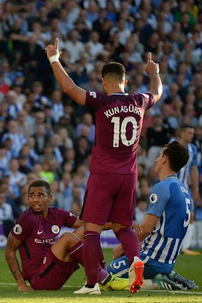 Brighton's Lewis Dunk (R) reacts after scoring an own goal as Manchester City's Sergio Aguero (C) and Gabriel Jesus celebrate, during the English Premier League match at the American Express Community Stadium in Brighton, on August 12, 2017