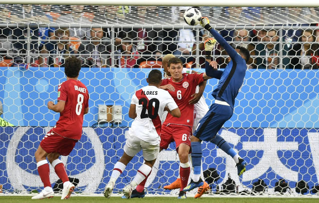 <p>Standing tall: Peru goalkeeper Pedro Gallese punches the ball clear under pressure. (AP) </p>