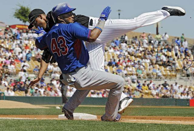Chicago Cubs' Emilio Bonifacio (43) collides with Chicago White Sox second baseman Marcus Semien covering first on a bunt in the first inning of a spring exhibition baseball game Friday, March 21, 2014, in Glendale, Ariz. (AP Photo/Mark Duncan)