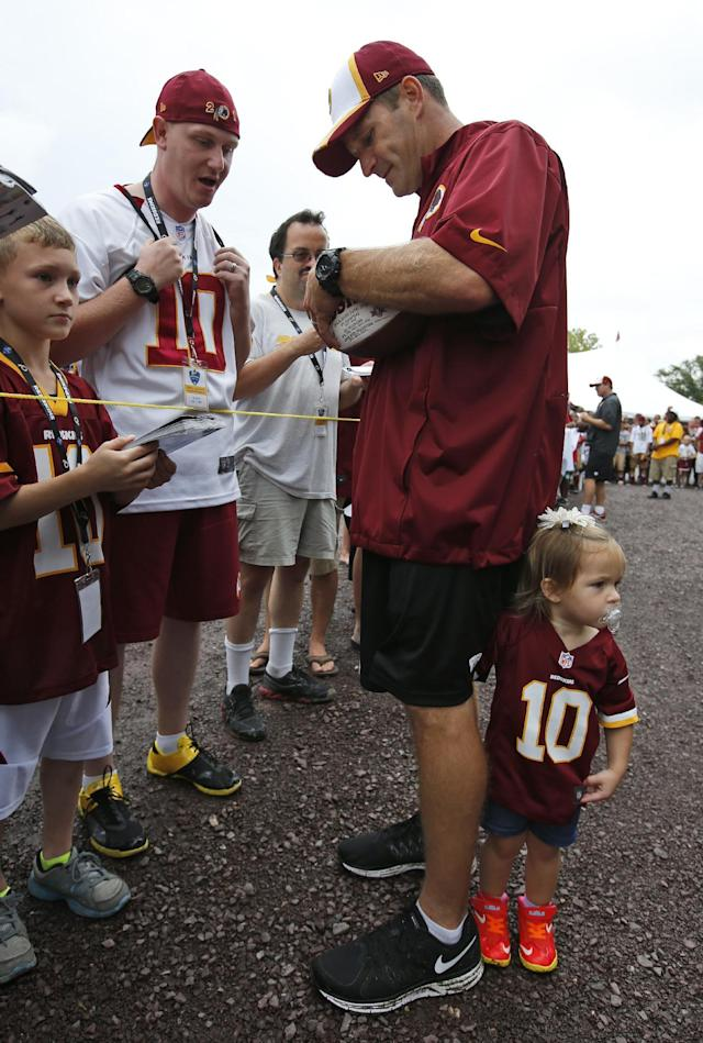 Washington Redskins special teams coach Ben Kotwica signs an autograph for a fan as his daughter Arianna Kotwica, 2, holds onto his leg after practice at the team's NFL football training facility, Sunday, July 27, 2014, in Roanoke, Va. (AP Photo/Alex Brandon)