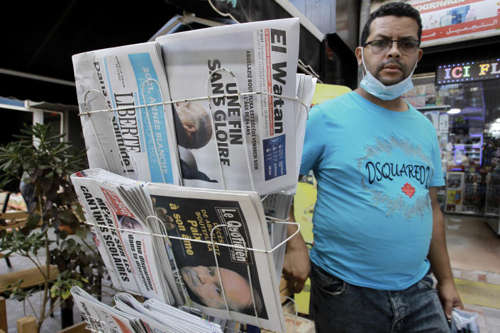 A man walks past newspapers headlining on former Algerian President Abdelaziz Bouteflika's death, in Algiers, Sunday, Sept.19, 2021. Algeria's leader declared a three-day period of mourning starting Saturday for former President Abdelaziz Bouteflika, whose 20-year-long rule, riddled with corruption, ended in disgrace as he was pushed from power amid huge street protests when he decided to seek a new term. Bouteflika, who had been ailing since a stroke in 2013, died Friday at 84. (AP Photo/Fateh Guidoum)