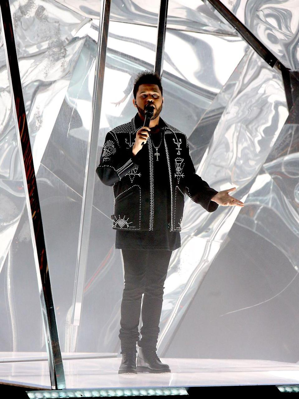 <p>Even performing live, Tesfaye rarely strays from what serves him best. Here he's snapped at the AMAs in an intricately detailed cropped jacket layered over a longer tee and stacked jeans, all in black. In other words, business as usual. </p>