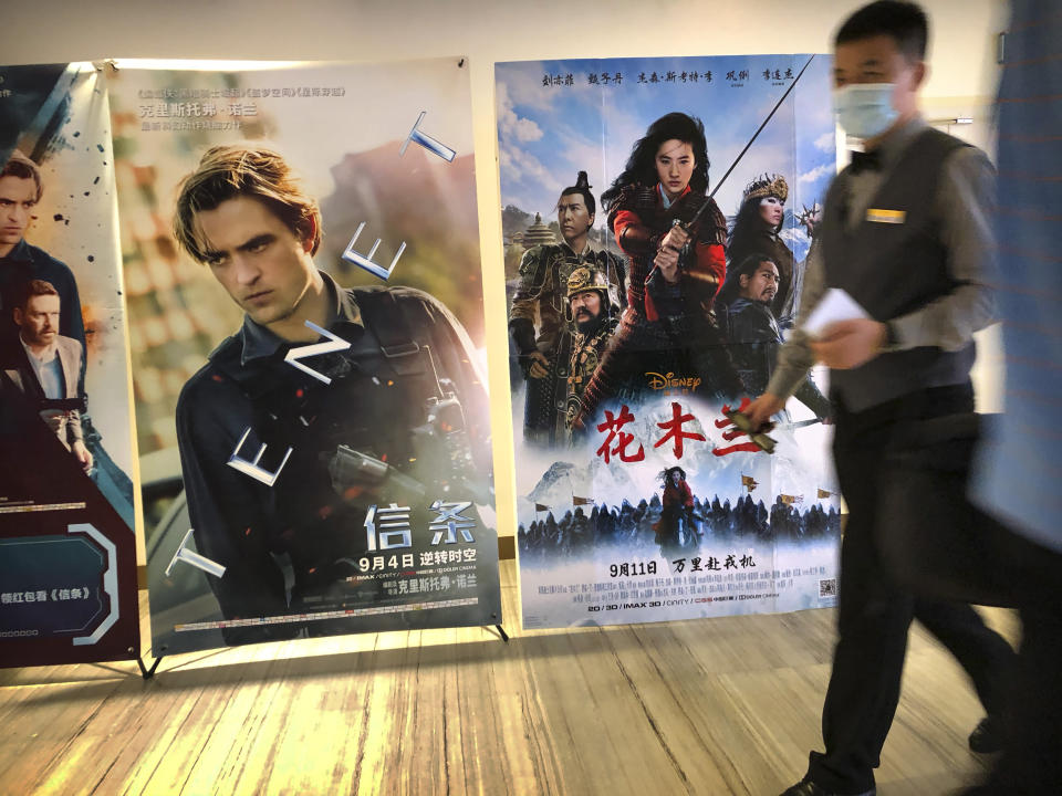 """An employee wearing a face mask walks past a poster for the Disney movie """"Mulan"""" at a movie theater in Beijing on Sept. 11, 2020. The remake of """"Mulan"""" struck all the right chords to be a hit in the key Chinese market. Disney cast beloved actresses Liu Yifei as Mulan and removed a popular dragon sidekick in the original to cater to Chinese tastes. (AP Photo/Mark Schiefelbein)"""