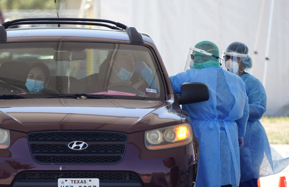 Medical personnel administer COVID-19 testing at a drive-through site, Friday, Aug. 14, 2020, in San Antonio. Coronavirus testing in Texas has dropped significantly, mirroring nationwide trends, just as schools reopen and football teams charge ahead with plans to play. (AP Photo/Eric Gay)