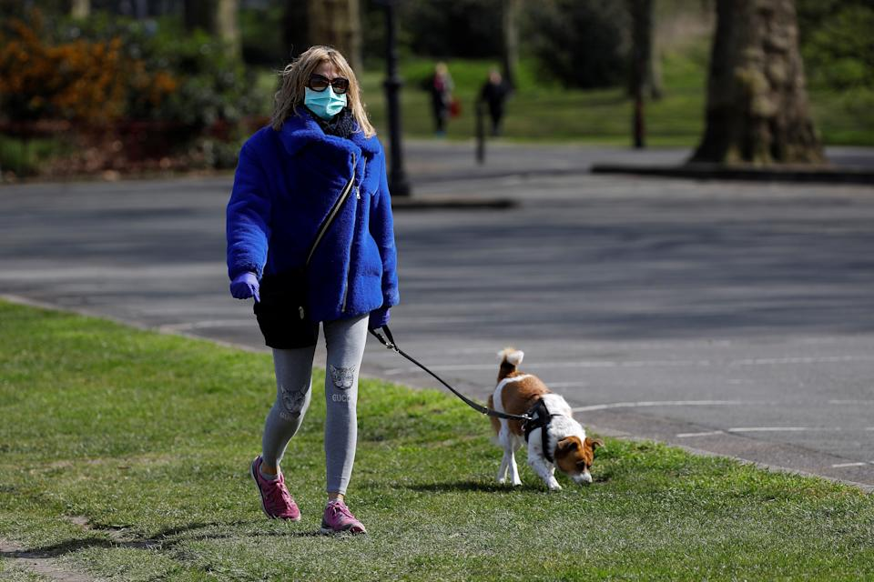 A woman wearing a face mask as a precautionary measure against Covi-19,=m=, walks a dog to get her exercise in Battersea Park in London on March 28, 2020, as life continues in Britain during the novel coronavirus pandemic. - The two men leading Britain's fight against the coronavirus -- Prime Minister Boris Johnson and his Health Secretary Matt Hancock -- both announced Friday they had tested positive for COVID-19, as infection rates accelerated and daily death rate rose sharply. (Photo by Tolga AKMEN / AFP) (Photo by TOLGA AKMEN/AFP via Getty Images)