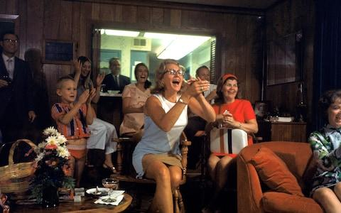 Joan Aldrin, centre, applauds her husband's arrival back to Earth as she watches TV coverage - Credit: GETTY IMAGES