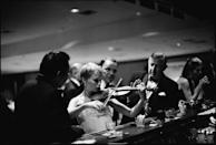 <p>Mia Farrow stuns partygoers by playing the violin at the bar of the Sands hotel in Las Vegas. Her husband, Frank Sinatra, looks on. The couple was attending festivities held for actress Rosalind Russell. </p>