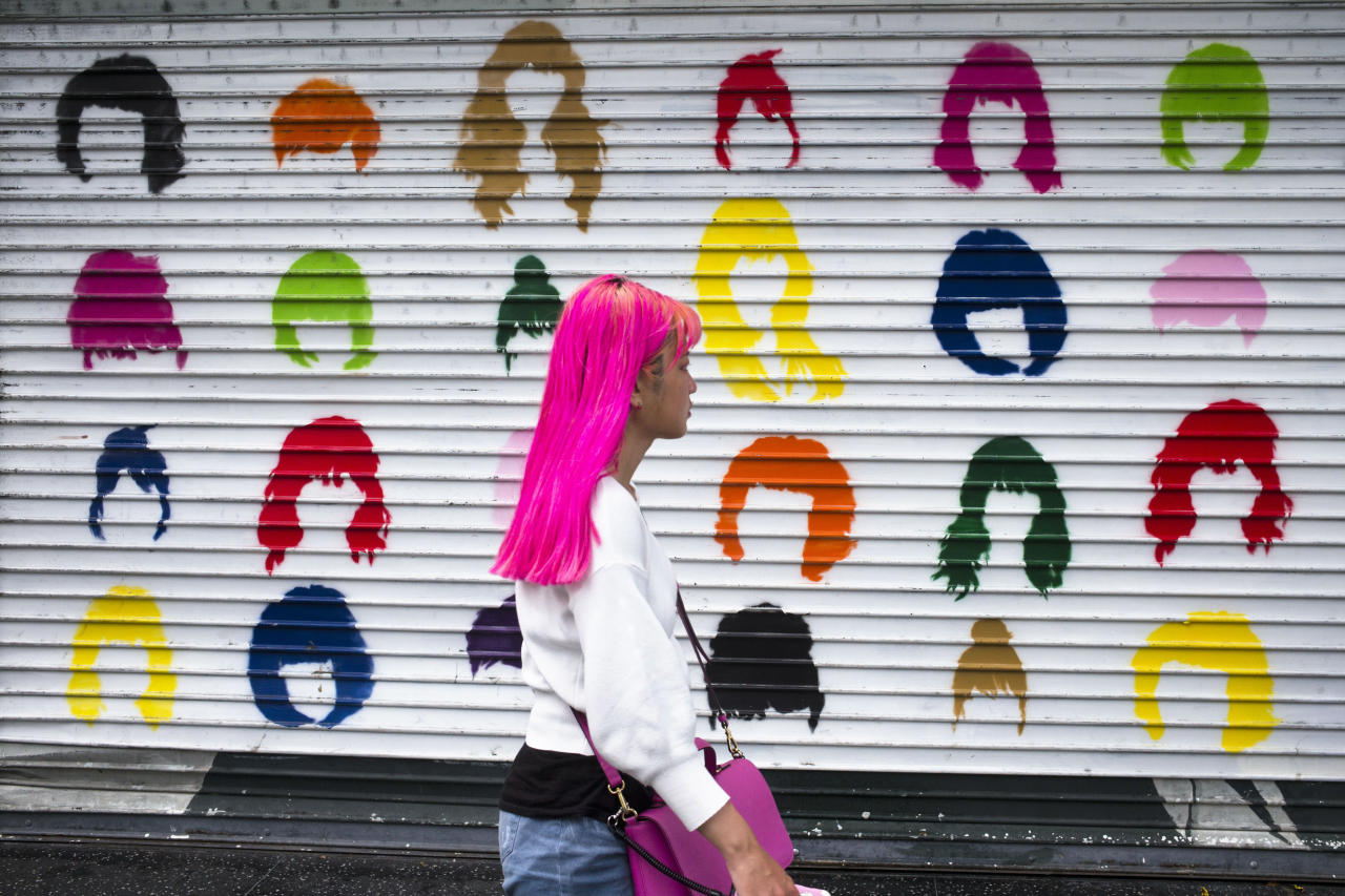 A woman with pink hair walks along Hollywood Boulevard past a colorful storefront shutter Wednesday, July 18, 2018, in Los Angeles. (AP Photo/Jae C. Hong)