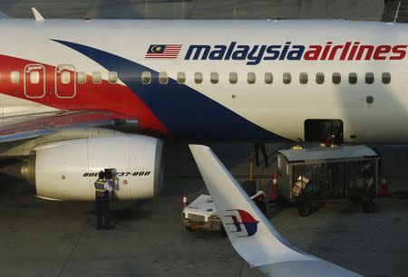 A member of ground crew works on a Malaysia Airlines Boeing 737-800 airplane on the runway at Kuala Lumpur International Airport in Sepang