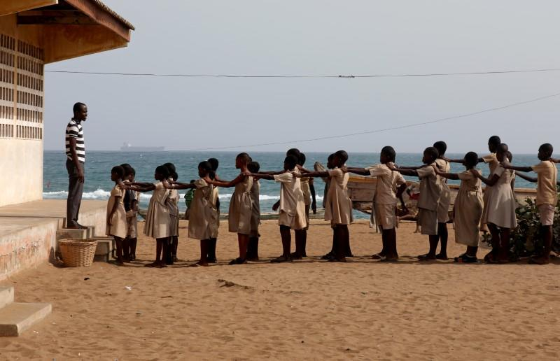 Pupils line up in the yard of their school, which was damaged by sea storms, in Baguida