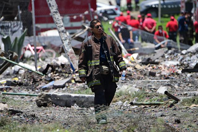 <p>A firefighter walks at the site of a series of explosions at fireworks warehouses in Tultepec, central Mexico, on July 5, 2018. – At least 19 people were killed, including rescue workers who died saving others' lives, officials said. The initial explosion occurred around 9:30 am (1430 GMT), then spread to other warehouses just as police and firefighters began attending to the first victims. (Photo: Pedro Pardo/AFP/Getty Images) </p>