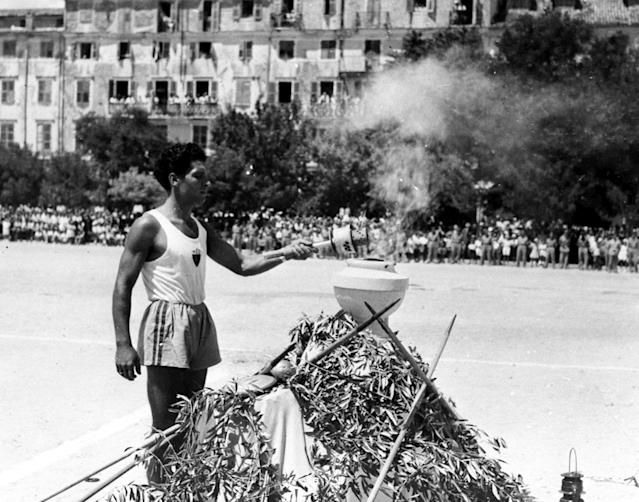 "Olympic torch bearer lights the ""Liohnos"", sacred vase, in which the flame will be preserved, in the Public Square, Corfu, July 18, 1948, and wil then be taken to the British frigate HMS Whitesand Bay to be transported to Bari, Italy. The flame is due at Wembley Stadium, in London, for the opening ceremony of the XIV Summer Olympic Games on July 29. (AP Photo)"