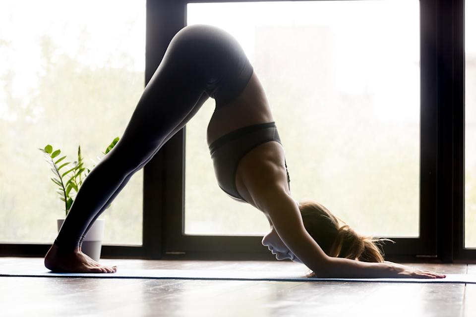 Young sporty woman practicing yoga, doing variation of Downward facing dog exercise, adho mukha svanasana pose, working out, wearing sportswear, grey pants and top, indoor full length, yoga studio