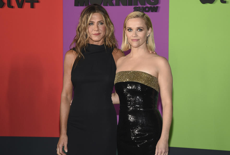 """Jennifer Aniston, left, and Reese Witherspoon attend the world premiere of Apple's """"The Morning Show"""" at David Geffen Hall on Monday, Oct. 28, 2019, in New York. (Photo by Evan Agostini/Invision/AP)"""