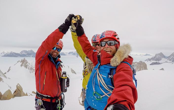 Friends Leo Houlding (right), Jean Burgun (centre) and Mark Sedon celebrate making it to the top of the Sceptre. (SWNS)