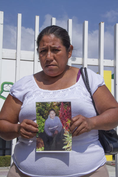 Roselia Rios Cueto, holds up a photo of her son, Ezequiel Cordoba Rios in Tuxtla Gutierrez, Mexico, Thursday Feb. 6, 2014. Cordoba was the Mexican fisherman who died during a reported 13-month sea odyssey with Jose Salvador Alvarenga. Alvarenga, a Salvadoran fisherman, said Cordoba died early in the voyage and that he tossed Cordoba body overboard, while he survived by eating fish, turtles and birds. (AP Photo/Moyses Zuniga)
