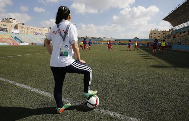 Palestinian woman stands over a ball before a qualifying match against Thailand in the West Bank town of al-Ram on April 3, 2017 (AFP Photo/ABBAS MOMANI)