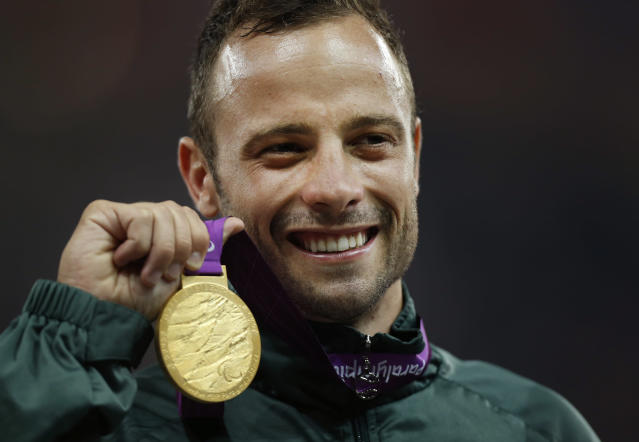 Gold medalist South Africa's Oscar Pistorius poses with his medal during the ceremony after winning the men's 400 meters T44 category final during the athletics competition at the 2012 Paralympics, Saturday, Sept. 8, 2012, in London. (AP Photo/Matt Dunham)