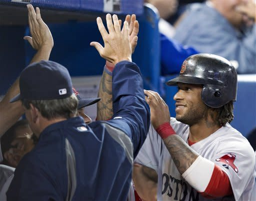 Boston Red Sox pinch-runner Darnell McDonald is congratulated by teammates after scoring against the Toronto Blue Jays during the ninth inning of a baseball game in Toronto on Monday, April 9, 2012. (AP Photo/The Canadian Press, Frank Gunn)