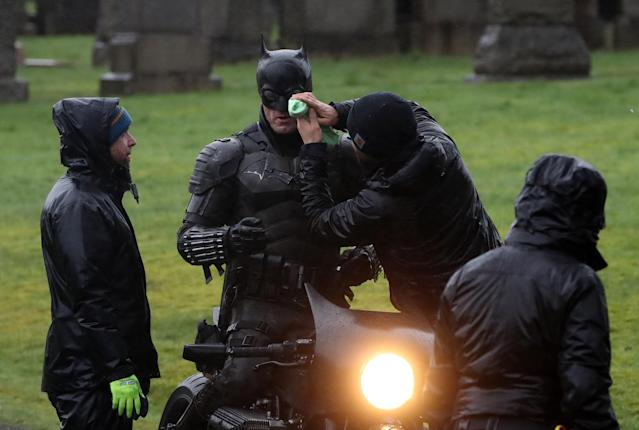 A man dressed as Batman has his face wiped during filming at the Glasgow Necropolis, February 2020. (Andrew Milligan/PA Images via Getty Images)