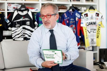President of Lombardy Roberto Maroni shows a brochure promoting Lombardy autonomy referendum during an interview with Reuters in his office in Milan, Italy, October 12, 2017. REUTERS/Alessandro Garofalo